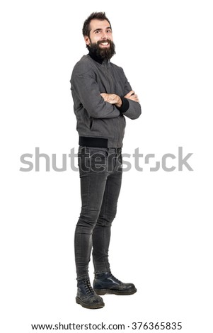Funny laughing bearded man in tight jeans and army boots looking at camera. Full body length portrait isolated over white studio background.
