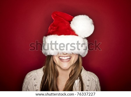 Funny Laughing Christmas girl with red fluffy Santa Hat - stock photo