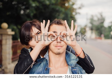 Funny laughing couple, sensual fashion portrait of young couple in love, having fun, relaxed end end enjoy time together at the street, beautiful sunset, elegant trendy clothes, romantic atmosphere.  - stock photo