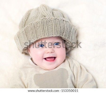 Funny laughing little baby wearing a big knitted hat and a warm sweater having fun relaxing on a white blanket - stock photo