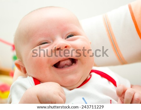 Funny laughing newborn european boy on a grandma hands - stock photo