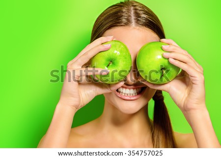 Funny laughing woman holding two gren apples before her eyes. Green background. Healthy eating concept. Diet. - stock photo