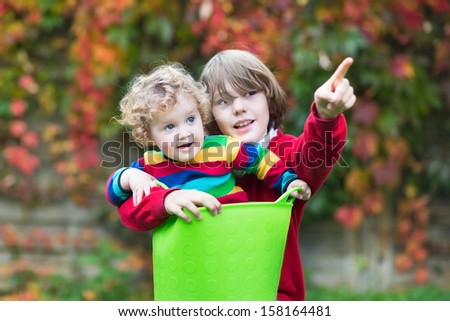 Funny little baby girl and her brother playing together in the garden - stock photo