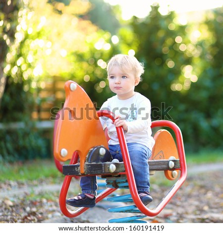 Funny little baby girl having on the playground riding on the spring horse - stock photo