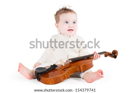 Funny little baby girl playing with a big violin on white background