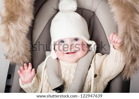 Funny little baby in a warm hat sitting in a stroller - stock photo