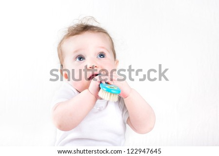 Funny little baby playing with a hair brush - stock photo
