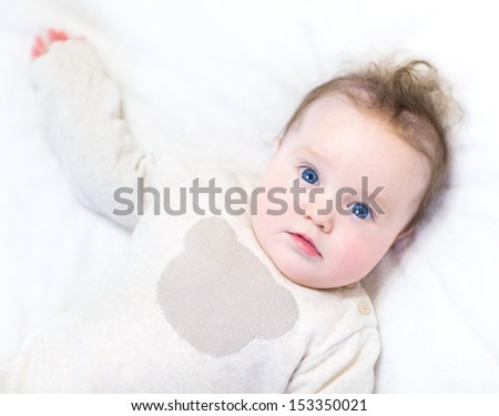 Funny little baby wearing a warm knitted sweater relaxing on a white blanket - stock photo