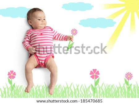 Funny little baby with drawn flower on meadow - stock photo