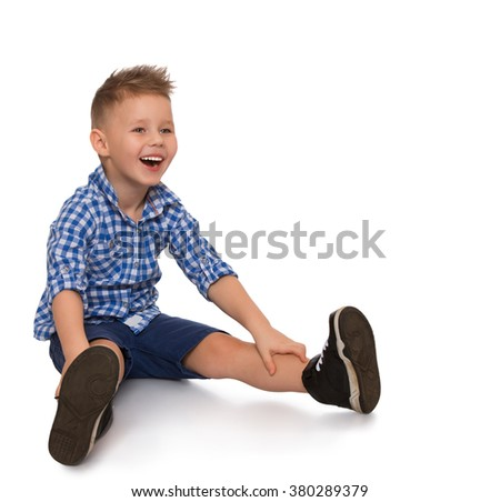 Funny little blond boy sitting on the floor. He cheerfully laughs - Isolated on white background - stock photo