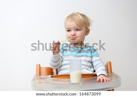 Funny little blonde toddler girl in blue stripes sweater drinking milk from the glass with straw sitting indoors in high feeding chair against white wall - stock photo