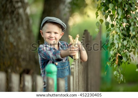 Funny little boy a bully in a cap and plaid shirt standing at a wooden fence shooting a slingshot - stock photo