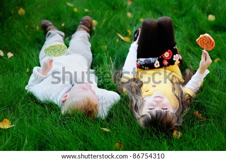 Funny little boy and girl eating big lollipops on a stick lying together on a lawn