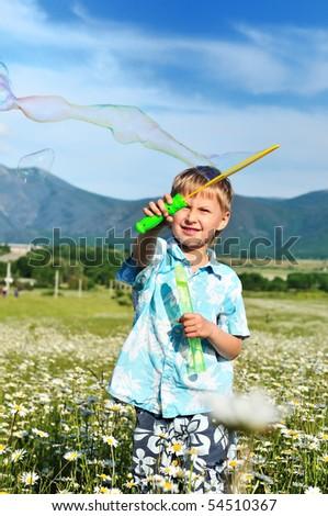 funny little boy blowing soap bubbles  in daisy field - stock photo