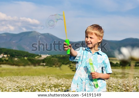 funny little boy blowing soap bubbles outdoors - stock photo