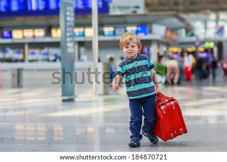 Funny little boy going on vacations trip with suitcase at airport, indoors. - stock photo