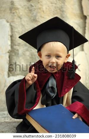 funny little boy graduate of the University - stock photo