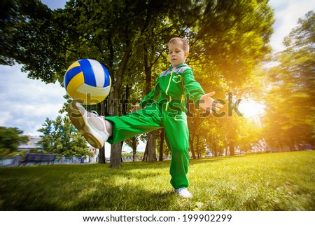 Funny little boy having fun playing soccer with ball - stock photo