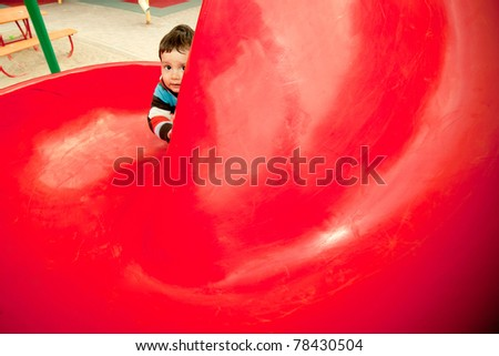 funny little boy hiding in the playground of the children's slide