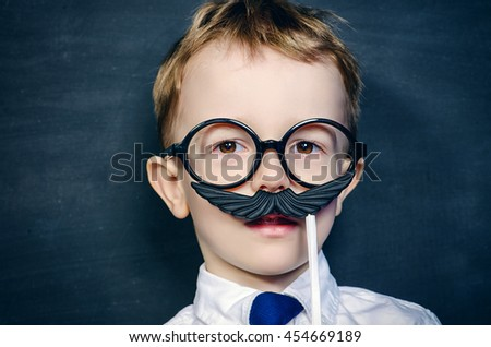 Funny little boy in round glasses plays with false mustache. Childhood concept. Emotions.  - stock photo