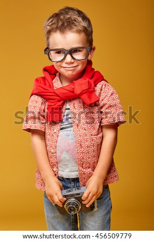 Funny little boy in studio wearing jeans and glasses