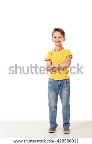 Funny little boy is looking at camera and smiling while standing with crossed arms, isolated on a white background - stock photo