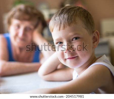 Funny little boy looking at the camera (grandmother to blured in the background) - stock photo
