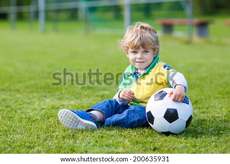 Funny little boy of 3 having fun with playing soccer with football on football field, outdoors.
