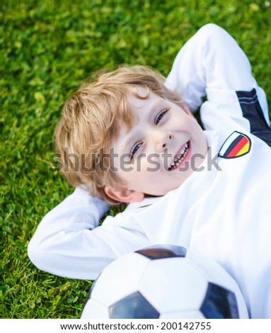 Funny little boy of 4 resting after playing soccer with football on football field, outdoors. - stock photo