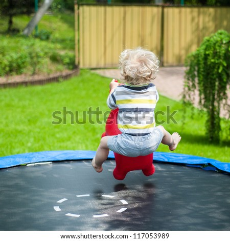 Funny little boy on trampoline - stock photo
