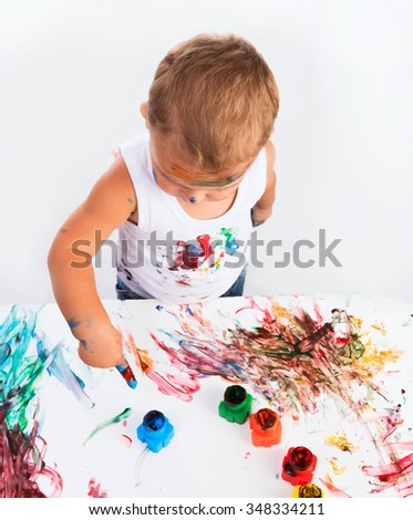 funny little boy painting with hands paper and himself on a white background - stock photo