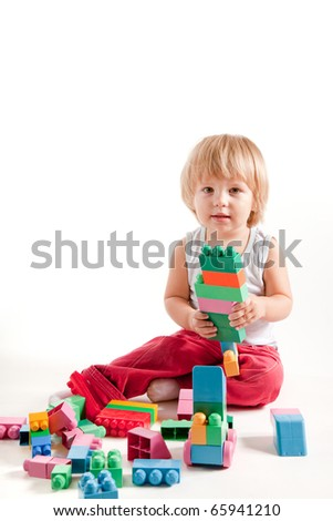 Funny little boy playing with blocks, studio shot - stock photo