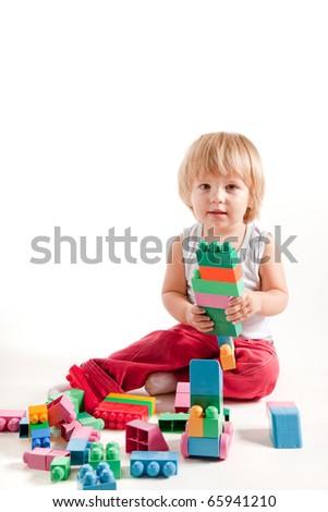 Funny little boy playing with blocks, studio shot - stock photo