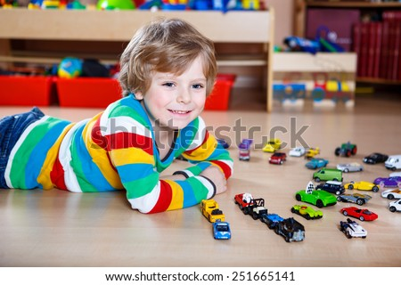 Funny little boy playing with lots of toy cars indoor, at home or at nursery. Kid boy wearing colorful shirt and having fun. - stock photo