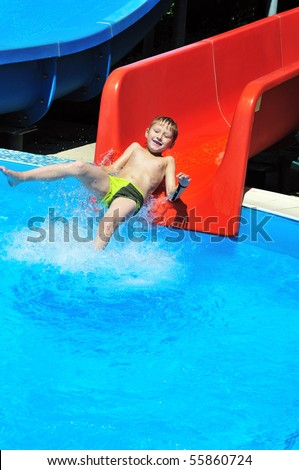 funny little boy sliding down a water slide - stock photo