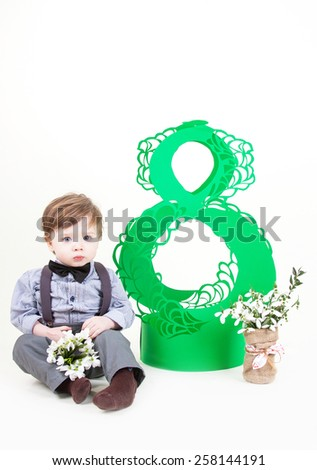 Funny little boy with snowdrops in hands sitting and smiling - stock photo