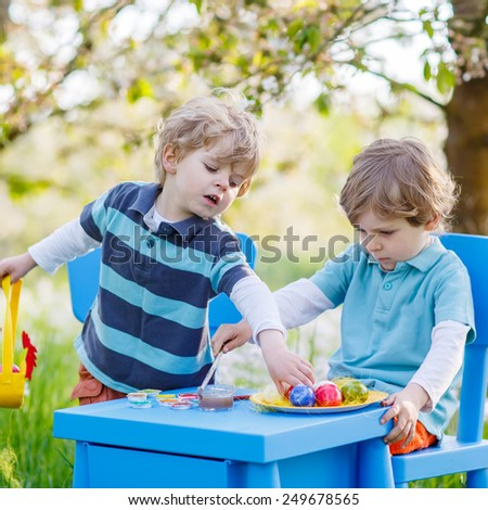 Funny little boys playinig and painting colorful eggs and having fun outdoors. Celebration of traditional Easter holiday in Europe. On warm sunny spring day. - stock photo
