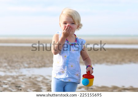 Funny little child, adorable blonde toddler girl wearing colorful necklace playing on the beach at North Sea - stock photo