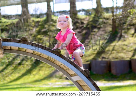 Funny little child, blond sportive toddler girl, having fun climbing on playground in the park on a sunny spring or summer day - stock photo