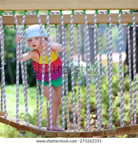 Funny little child, blond sportive toddler girl wearing colorful swimming suit, having fun climbing on playground in the park on a sunny summer day at vacation holidays resort - stock photo