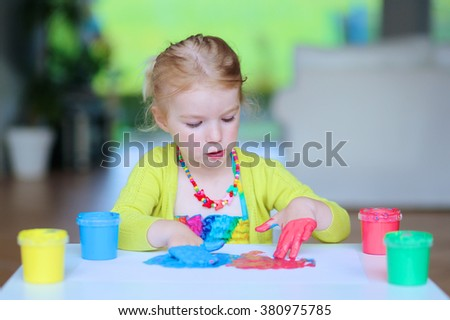 Funny little child, blonde artistic toddler girl painting and drawing with colorful finger paints indoors at bright room at home or kindergarten. - stock photo