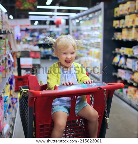 Funny little child, blonde toddler girl, sitting in the trolley during family shopping in hypermarket