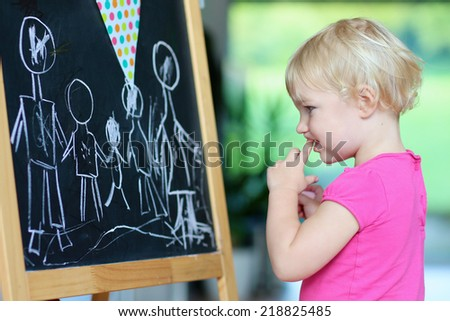 Funny little child, cute blonde toddler girl drawing family with chalk on black board standing in big bright room with garden view window - stock photo