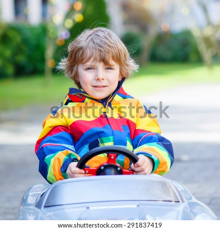 Funny little child driving big toy old vintage car and having fun, outdoors. Active leisure with kids outdoors  on warm spring or autumn day. - stock photo