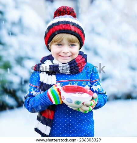 Funny little child holding big cup with snowflakes and hot cocoa and chocolate drink and marshmallows. Kid boy in winter sweater, cap, long warm scarf and colorful gloves. On cold winter day. - stock photo