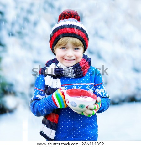 Funny little child holding big cup with snowflakes and hot cocoa and chocolate drink and marshmallows. Kid boy in winter sweater, cap, long warm scarf and colorful gloves. On cold winter day - stock photo