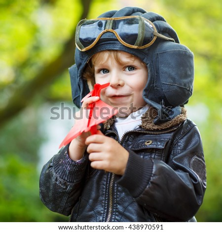 Funny little child in pilot helmet  and uniform playing with red toy airplane against green tree summer background. Kid boy having fun and dreaming of future profession.