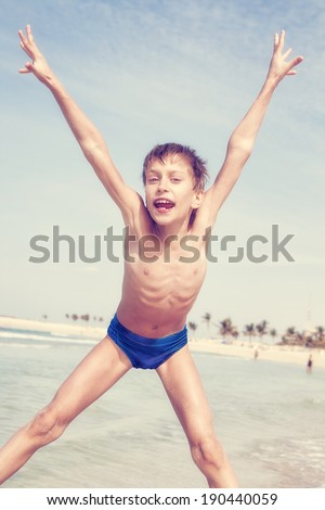 Funny little child jumping on the beach and laughing. Frozen motion.  - stock photo