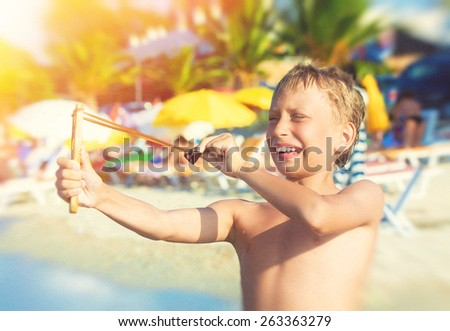 Funny little child playing on beach with a slingshot laughing. Summer vacation concept. - stock photo