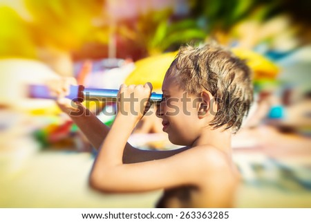 Funny little child playing on beach with a spyglass smiling. Tourism concept. - stock photo